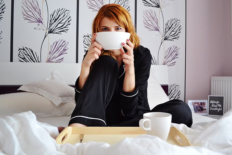 Woman in black pajama sitting on bed holding white bowl