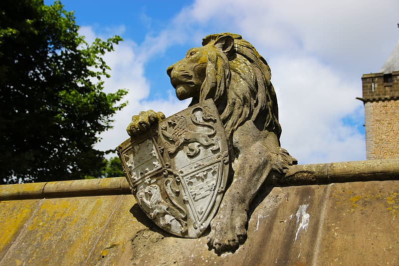 Brown lion holding a shield statue