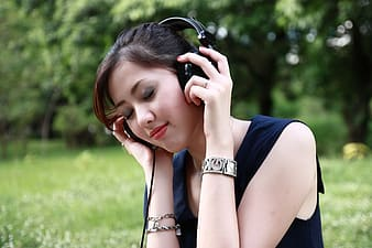 Woman listening to music while wearing headphones