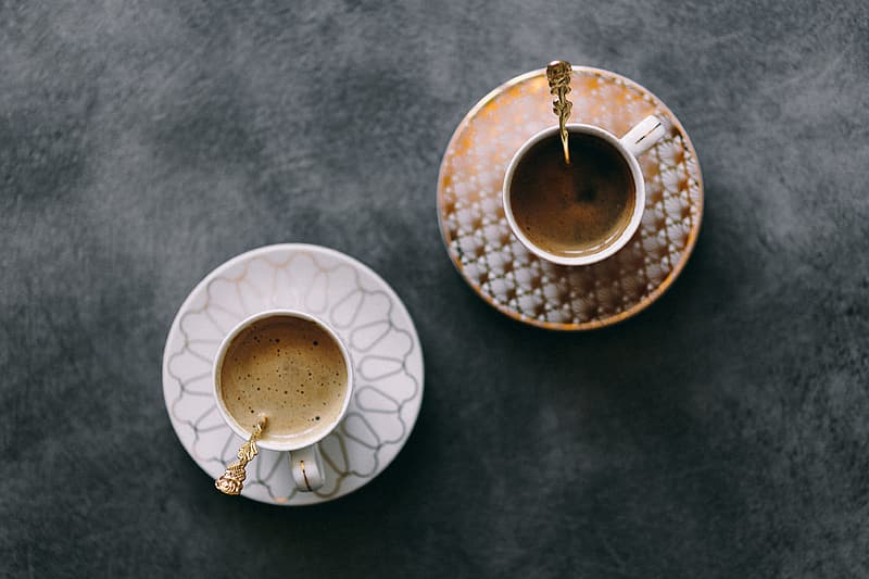 White ceramic cup with coffee on white ceramic saucer