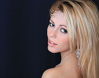 Woman with blonde hair wearing silver-colored accessories