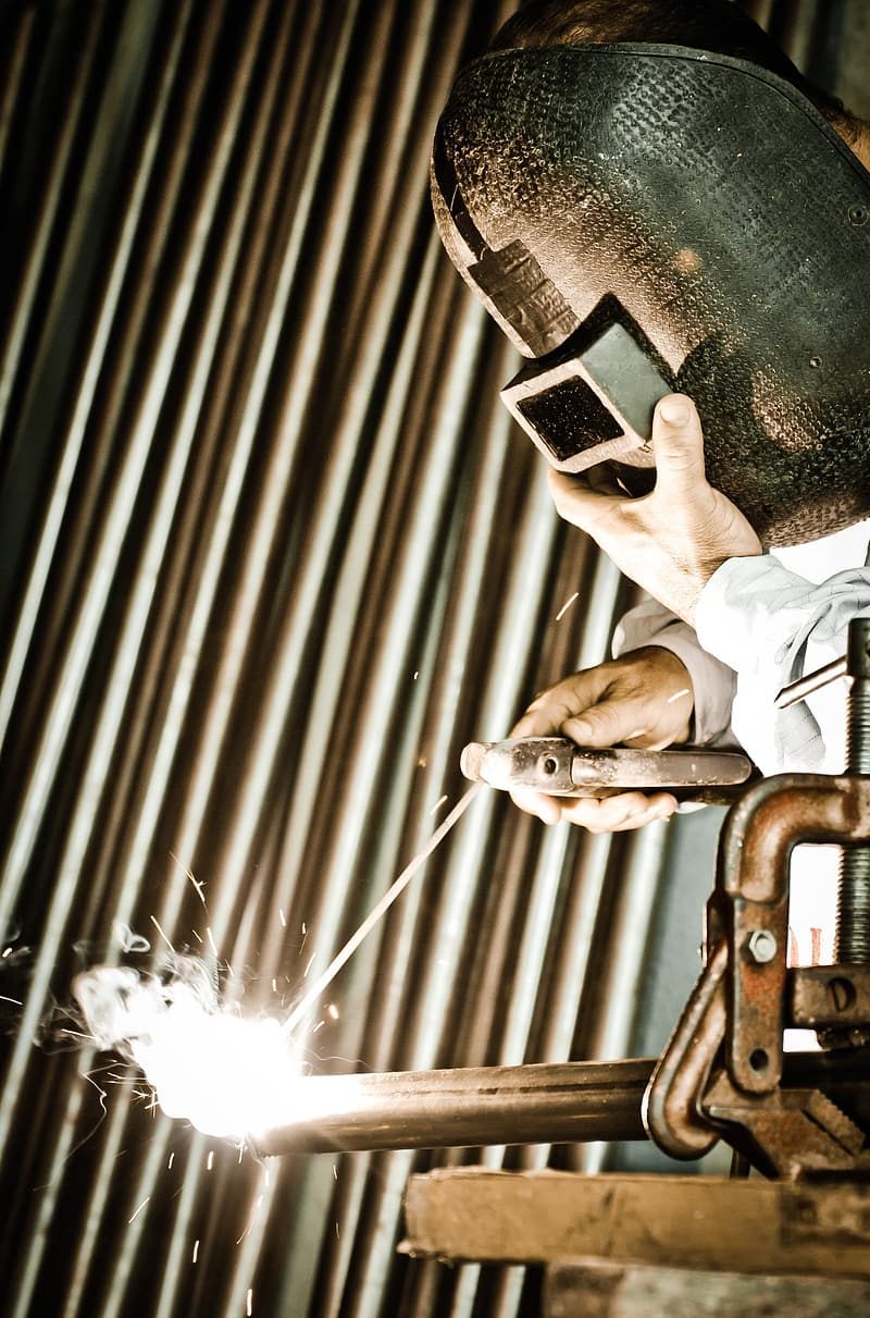 Person wearing gray welding mask welding a steel bar