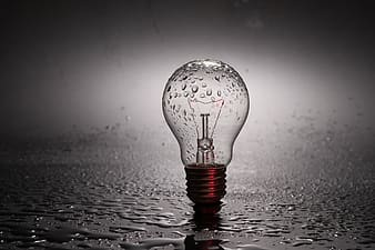 Clear light bulb on gray surface with water droplets