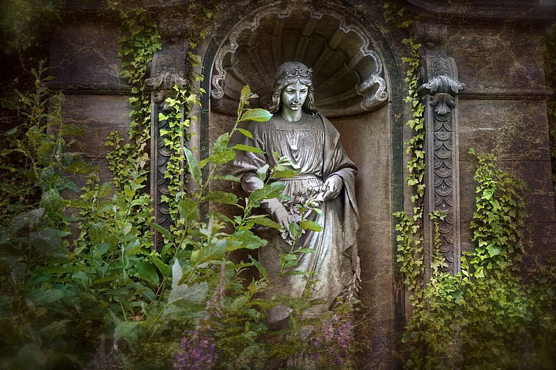 Religious statue between green leaf plant
