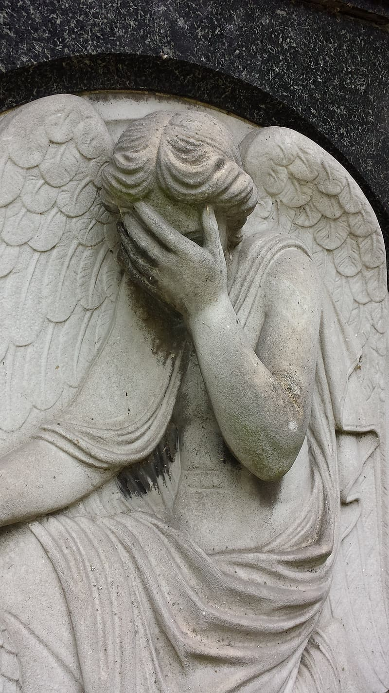 Female angel covering her face statue