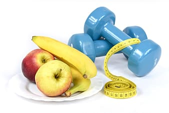 Two apples and two bananas served on white plate near two blue fixed weight dumbbells and tape measure