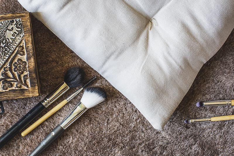 Five assorted makeup brushes beside white pillow