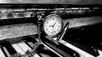 Round white and silver-colored pocket watch on top of piano