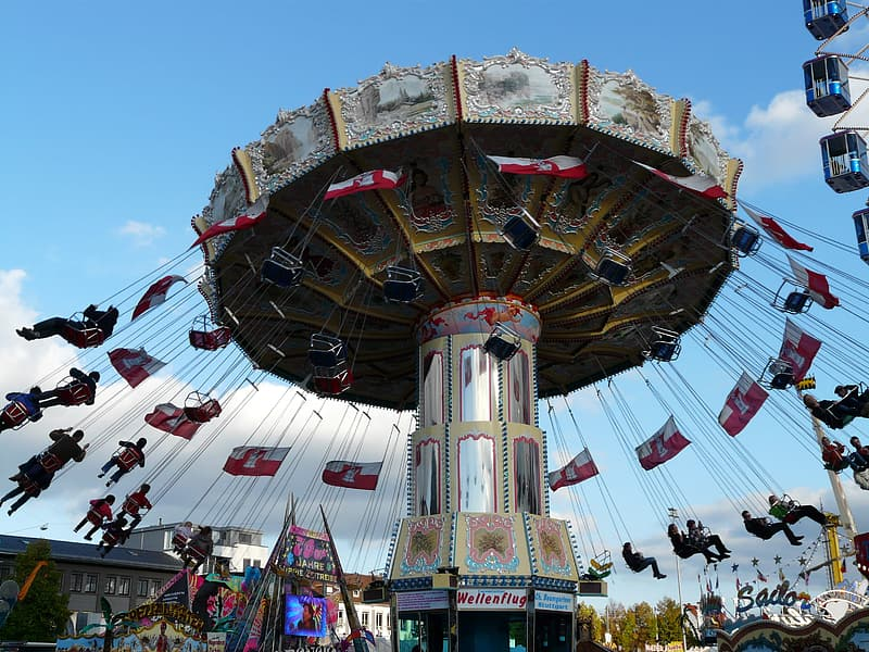 People riding on white and red carousel during daytime