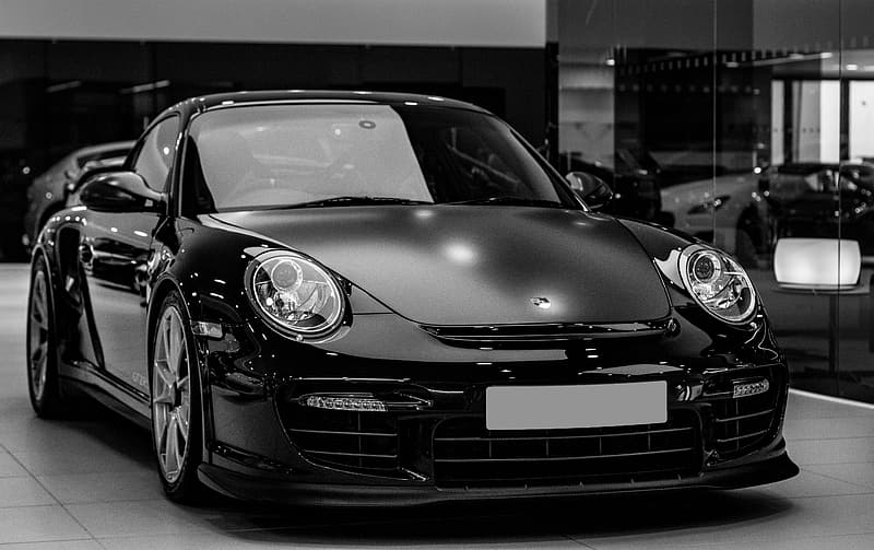 Grayscale photography of Porsche 911 coupe inside room