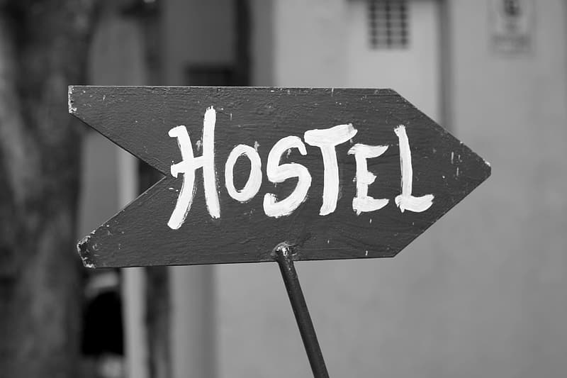 Grayscale photography of wooden hostel road signage