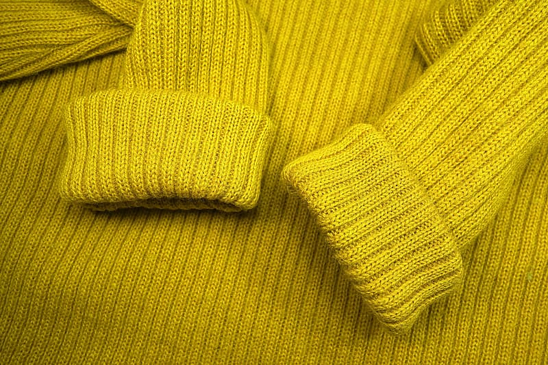 Yellow knit textile on brown textile