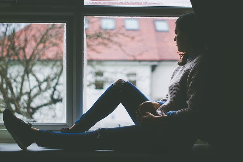 Woman in distressed denim jeans and sweater leaning beside wall post while watching outside the window