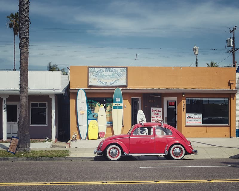 Red Volkswagen Beetle on road near store at daytime