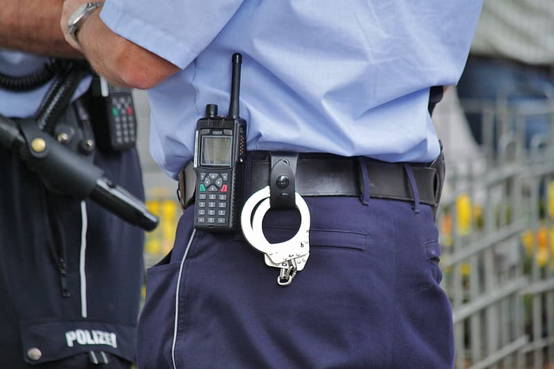 Police with handcuffs on black leather belt
