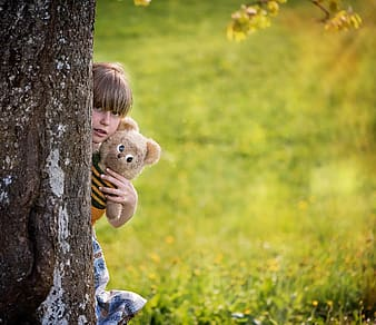 Child hiding behind the tree while holding brown bear plusht oy