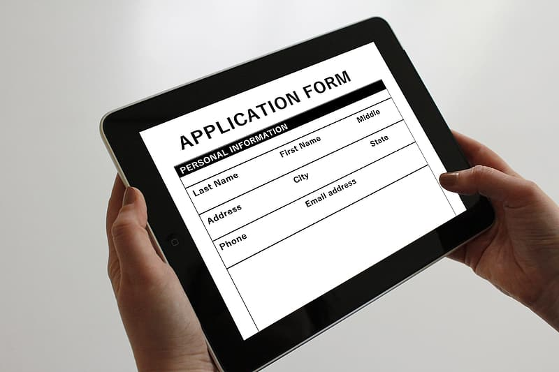 Person holding tablet displaying application form
