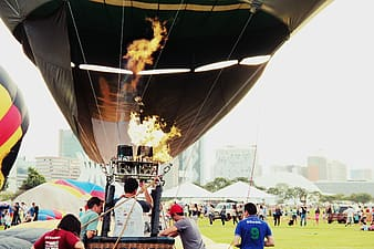 People near hot-air balloon and tents