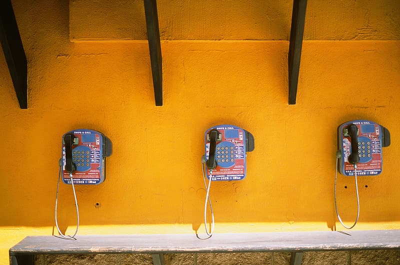 Red and black telephone on yellow wall