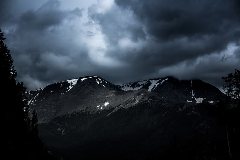 Snow-capped mountains under dark clouds