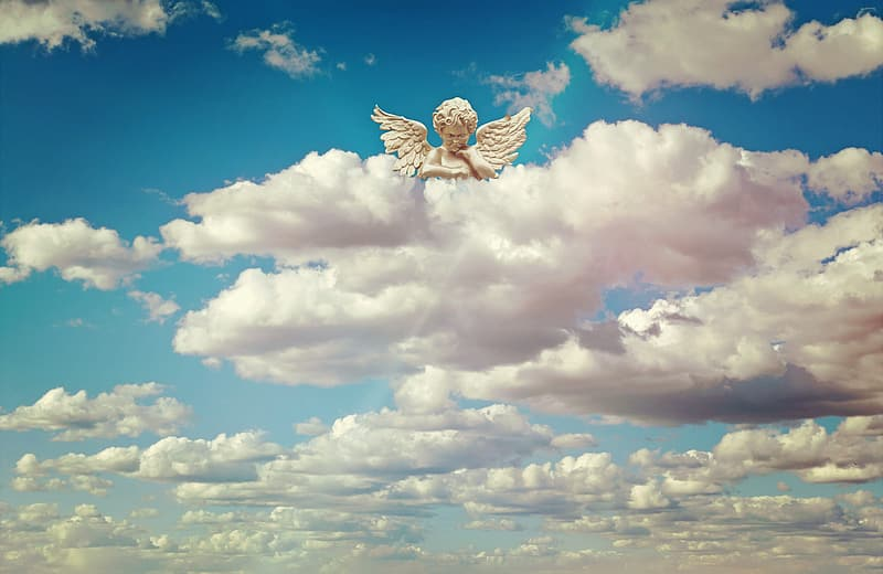 Angel statuette above white clouds at daytime