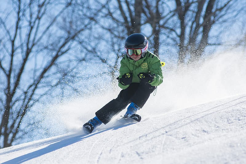 Person wearing green ski jacket and snow goggles skiing over snow ground with distance at bare trees during daytime