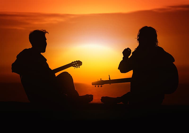 Silhouette of men playing guitar during sunset