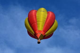 Worm's eyeview of yellow and red hot air balloon during daytime