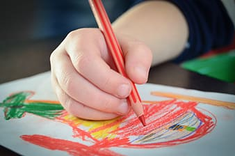 Person holding red colored pencil in shallow focus photography