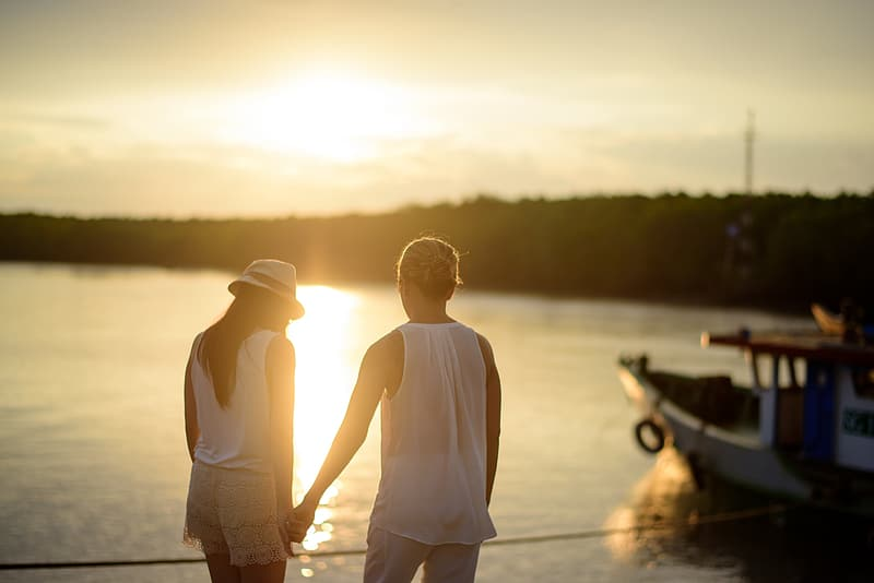 Man and woman holding hand beside body of water during daytime