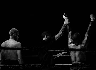 Referee raising up boxer's hand while the other boxer is standing behind