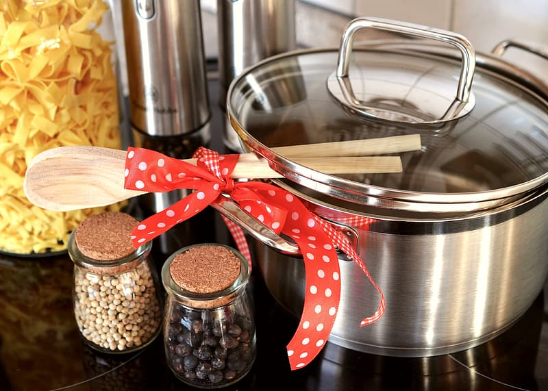 Gray stainless steel cooking pot and brown wooden ladles