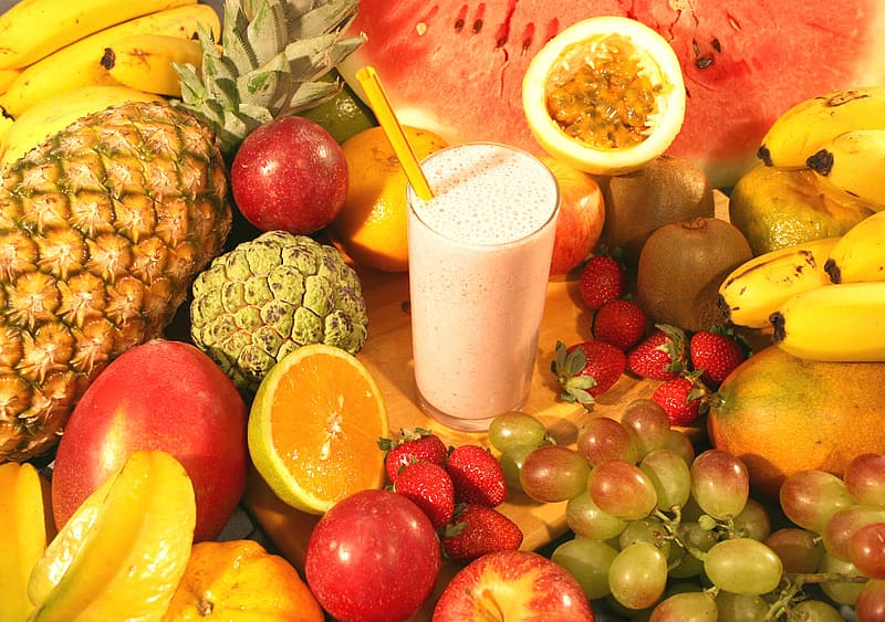 Milk drink surrounded by assorted fruits