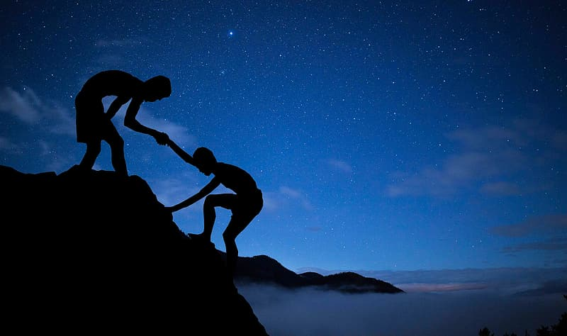 Silhouette of 2 men on top of rock formation under blue sky during night time