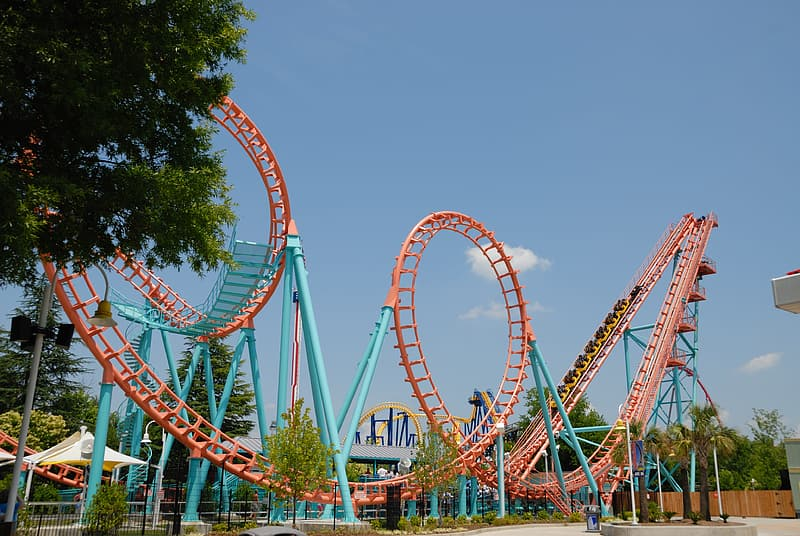 Red and teal roller coaster at daytime