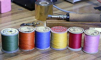 Assorted color thread on brown wooden table