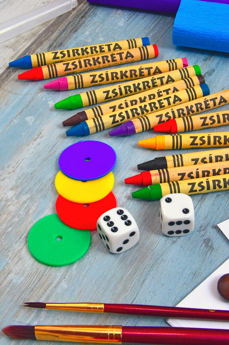White dice with assorted color coloring pencils