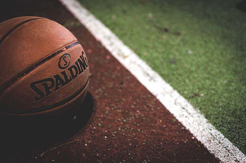 Brown and black basketball on brown and white concrete floor