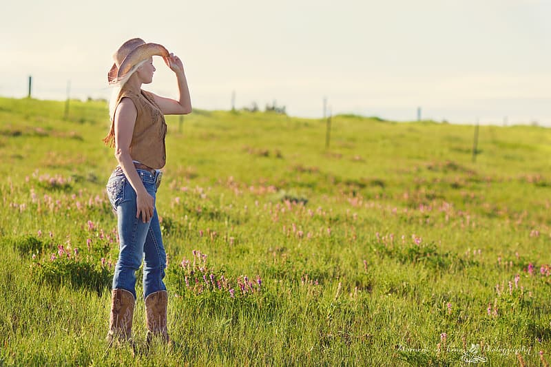 Woman standing on grass field holding her hat during daytime