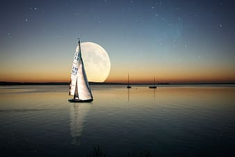 Sailboat on sea during night time