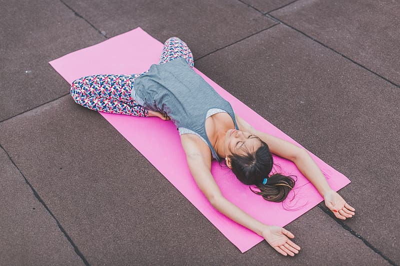 Woman wearing gray sleeveless top and multicolored leggings doing yoga