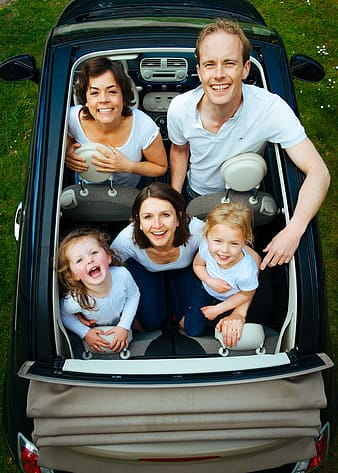 Photo of family in convertible car during daytime