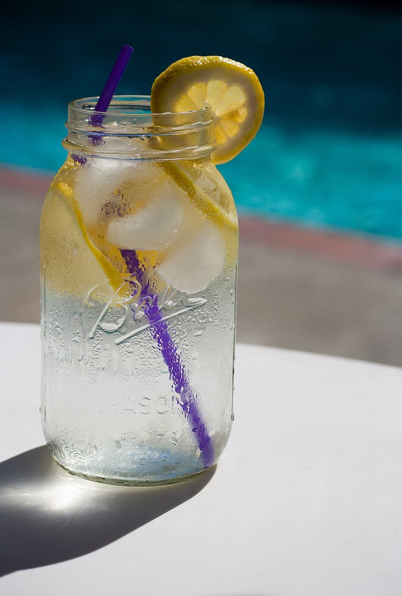 Selective focus photography of clear glass mason jar with lemonade and purple straw