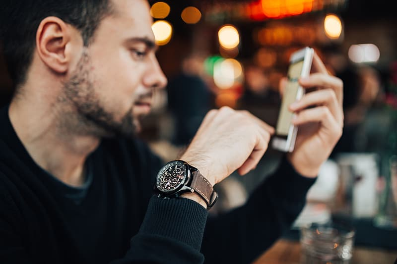 Man in black long sleeve shirt holding silver iphone 6