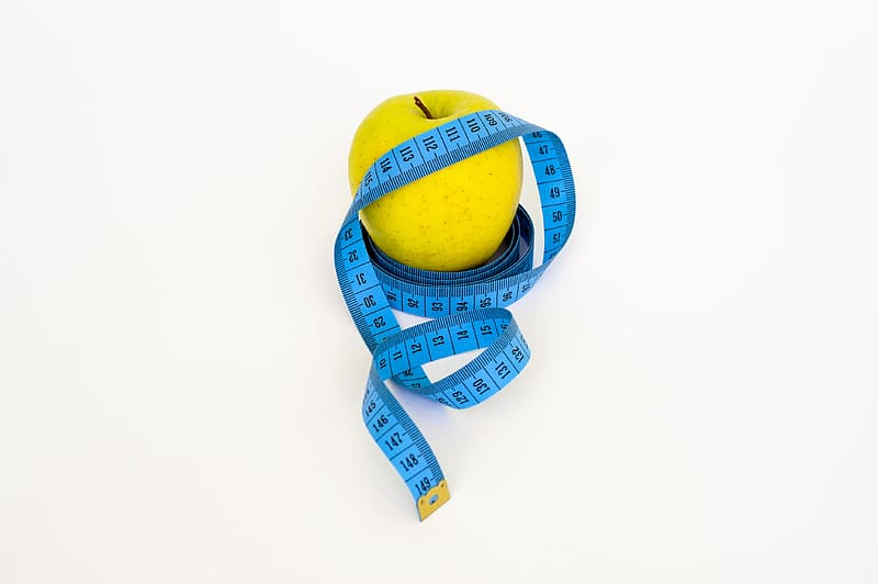 Green apple and blue tape measure