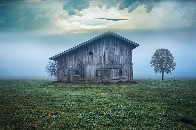 Brown wooden barn under blue sky and white clouds during daytime