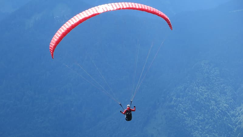 Person parachuting above body of water during daytime