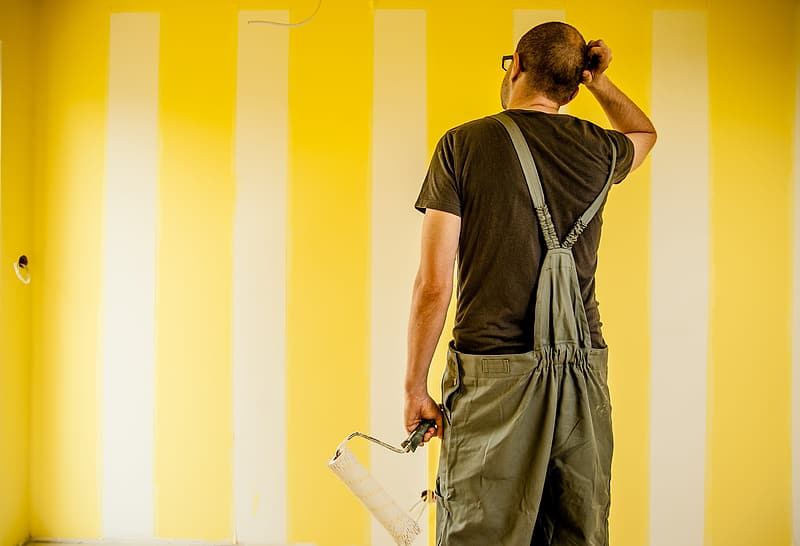 Man wearing brown shirt and overalls holding paint roller