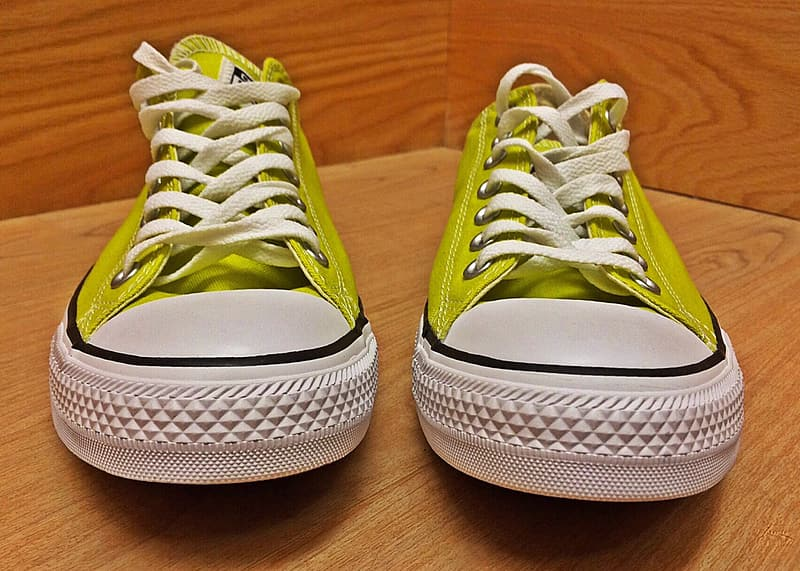 Pair of green Converse All-Star low-top sneakers on wooden surface