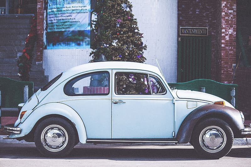 White volkswagen beetle parked near white concrete building during daytime